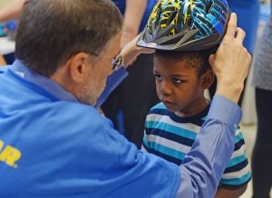Goodyear associate helps kid with bike helmet